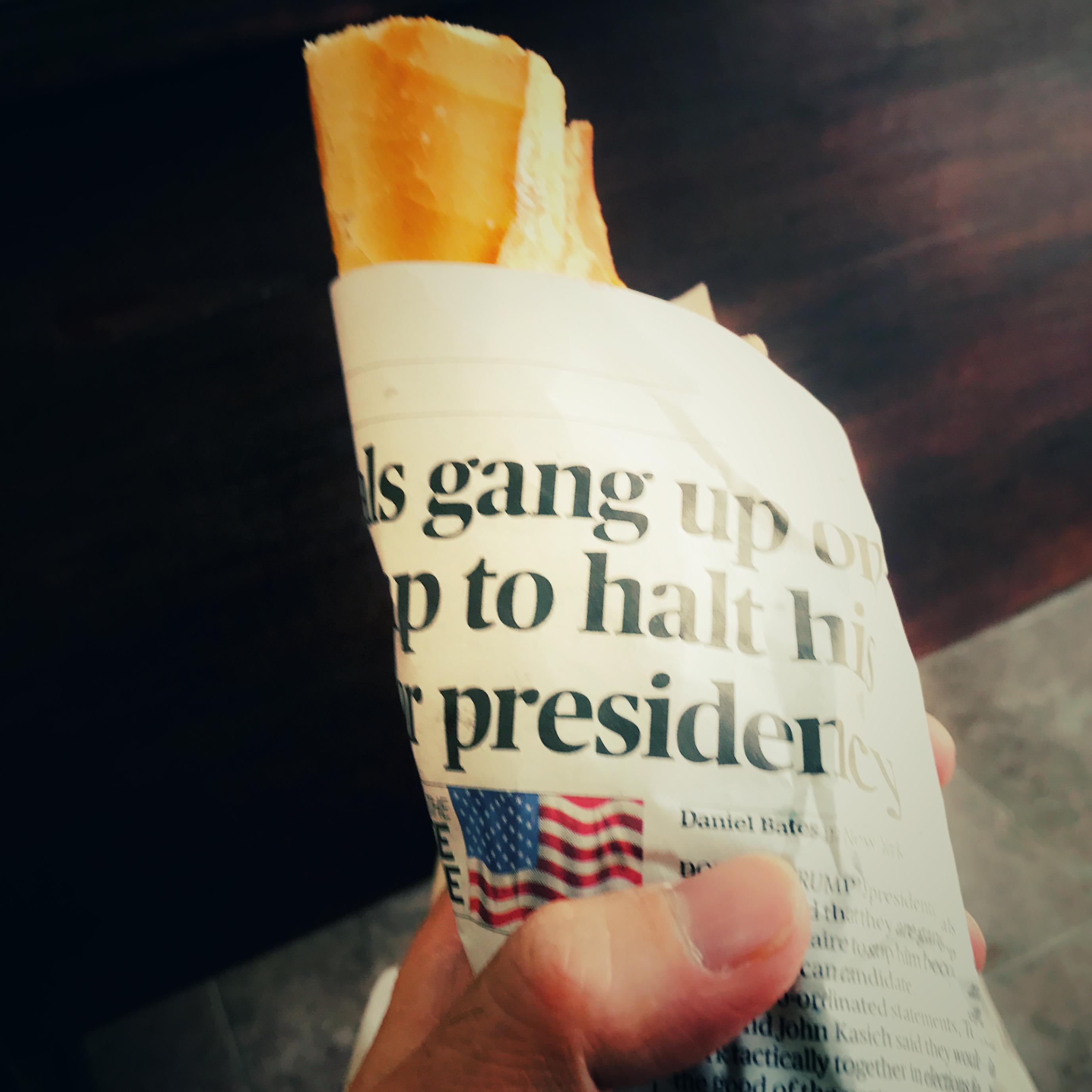 バケットを注文するとその場でチーズクリームをはさみ、タブロイド紙にくるんでサーブしてくれる